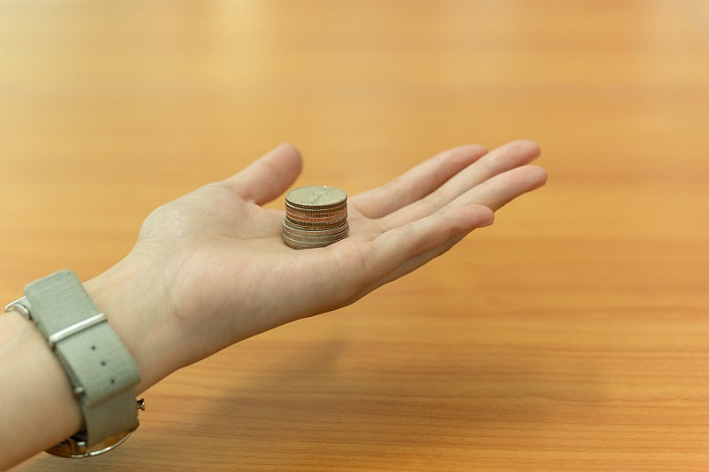 Open hand holding Thia coin on wooden table in background.
