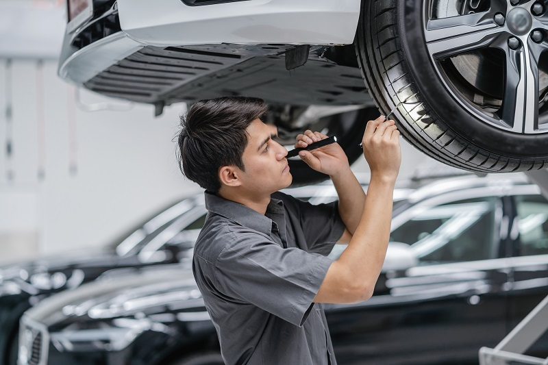 Asian mechanic Checking and torch tire in maintainance service c