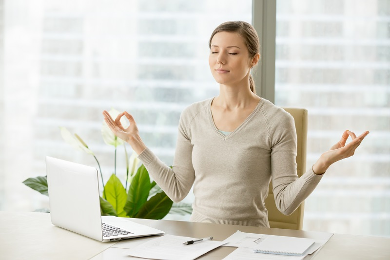 Calm businesswoman relaxing with breath gymnastics