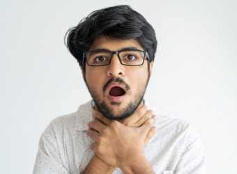 Scared Indian man keeping mouth open and chocking himself