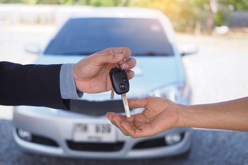 Car salesmen send keys to new car owners. Used car sales agency, car rental