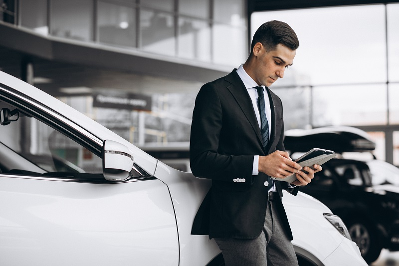 Young handsome man in car showroom