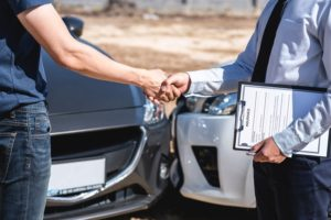 Insurance Agent and customer shaking hands after agreement about