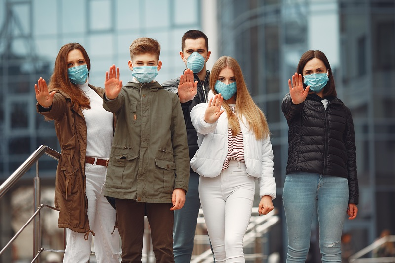 People wearing protective masks are showing stop sign by hands