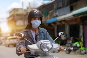 Woman riding a motorcycle wearing a mask in the city