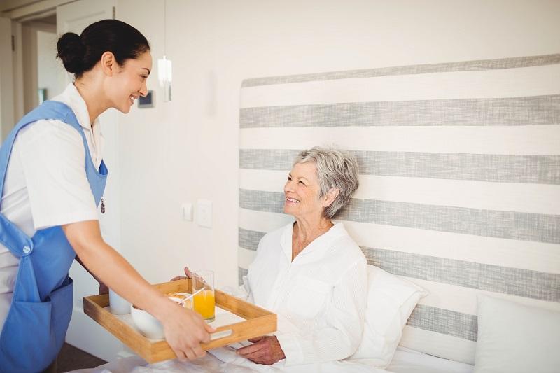 Nurse serving breakfast to senior woman in bedroom