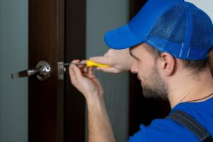 Handyman repair the door lock in the room. Closeup of man repairing the doorknob.