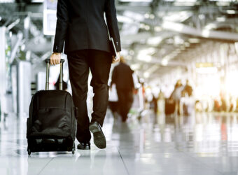 Businessman checking e-mail on mobile phone while walking with suitcase inside airport